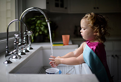 Side view of girl wearing pink cape washing hands in kitchen sink while standing at home - p1166m2067541 by Cavan Images