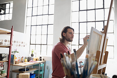 Male painter painting at canvas on easel in art studio - p1192m1490157 by Hero Images