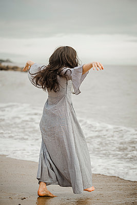 Woman with long dark hair and a long dress on the beach - p1628m2223335 by Lorraine Fitch