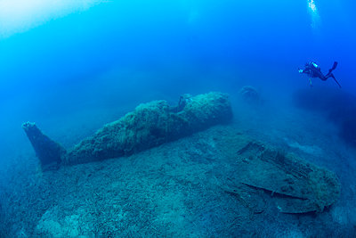 France, Corsica, Scuba diver swimming toward sunken wreck of P-47 Thunderbolt plane - p300m2154110 by Christian Zappel