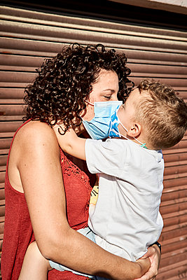 Mother carrying son with masks kissing him while standing against closed shutter - p300m2203173 by Veam