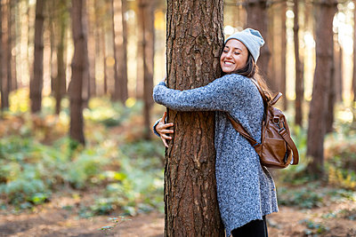 Happy female hiker embracing tree while hiking in Cannock Chase woodland during winter - p300m2241841 by William Perugini