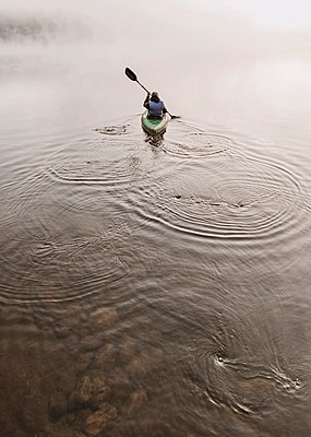 Young woman enjoys early morning paddle in kayak through mist on Daicey Pond in Maine's Baxter State Park, USA - p343m1569071 by Chris Bennett