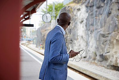 Businessman listening music while waiting at railroad station - p426m2072414 by Maskot