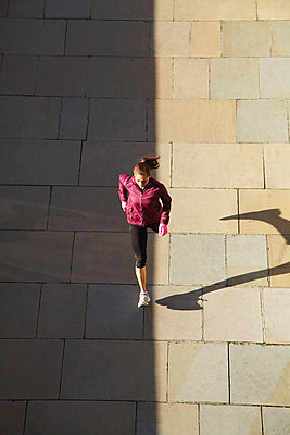 Woman running on city street - p429m800814f by Moof