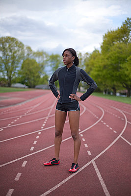Young female sprinter standing in lane - p4342615f by Alin Dragulin