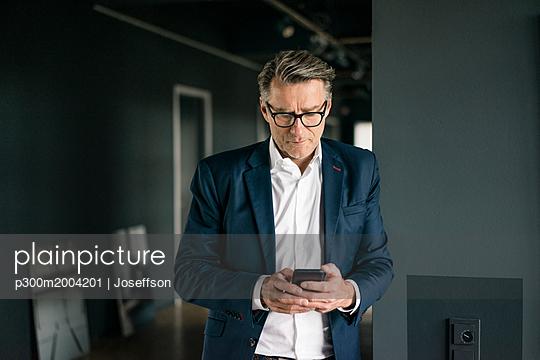 Mature businessman standing in office using cell phone - p300m2004201 von Joseffson