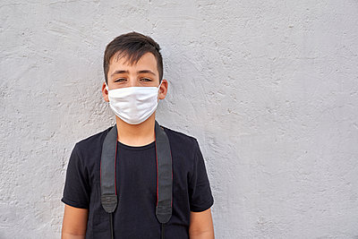 Boy with beautiful green eyes wearing a mask on the street - p1166m2201192 by Cavan Images