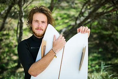 Australia, Queensland, Sunshine Coast, Noosa, Alexandria Bay, Portrait of young man holding surfboard - p352m1100906f by Jan Strandström