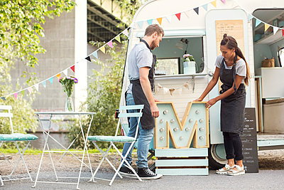 Owners placing letter M outside food truck on street - p426m1407071 by Maskot