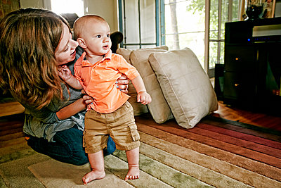 Caucasian mother helping baby walk on living room floor - p555m1420448 by Peathegee Inc