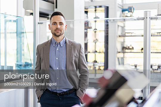 Portrait of confident businessman in a modern factory - p300m2103029 by Daniel Ingold