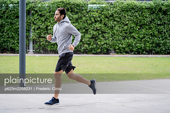 Young man jogging in park - p623m2258231 by Frederic Cirou