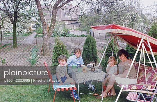 Deutschland, Familie beim Kaffeetrinken in der Hollywoodschaukel in der DDR - p986m2223985 von Friedrich Kayser