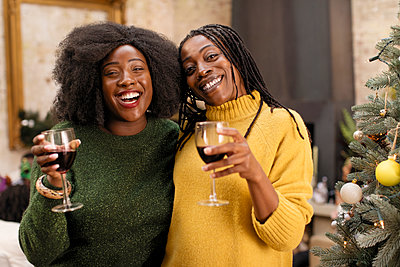 Portrait smiling, happy mother and daughter drinking wine next to Christmas tree - p1023m1575877 by Sam Edwards