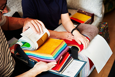 Two people sitting on a sofa, looking at a selection of fabric samples. - p1100m1177686 by Mint Images
