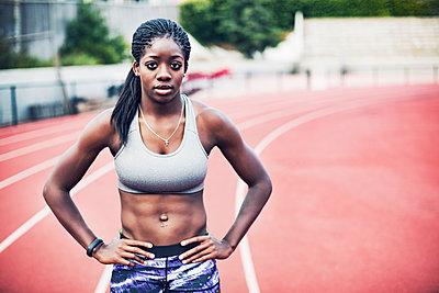 Portrait of confident sportswoman standing on running tracks - p1166m1086174f by John Trice