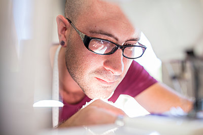 Close-up of man using sewing machine - p300m1581749 von zerocreatives