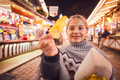 Portrait of smiling girl eating potato chip at carnival in city during night. Munich, Germany - p300m2197733 by Studio 27