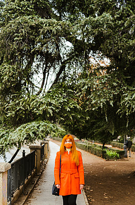 Woman with protective face mask standing against tree at public park - p300m2256135 by DREAMSTOCK1982