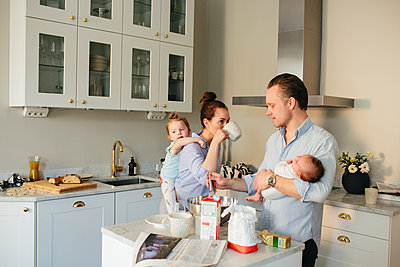 Family in kitchen - p312m1556882 by Anna Rostrom