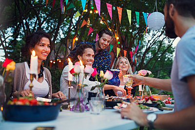 Multi-ethnic friends enjoying meal in back yard at garden party - p426m1226413 by Maskot
