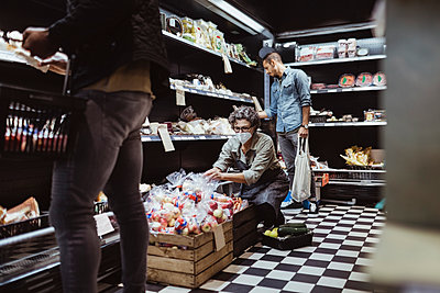 Male customer shopping while female owner crouching by in delicatessen store - p426m2270703 by Maskot