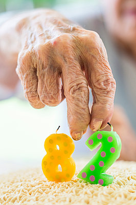 Close up of wrinkled hand holding birthday cake candle - p555m1311569 by Paco Navarro