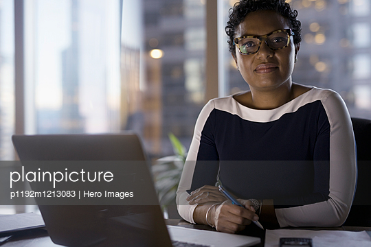 Portrait confident female lawyer working at laptop