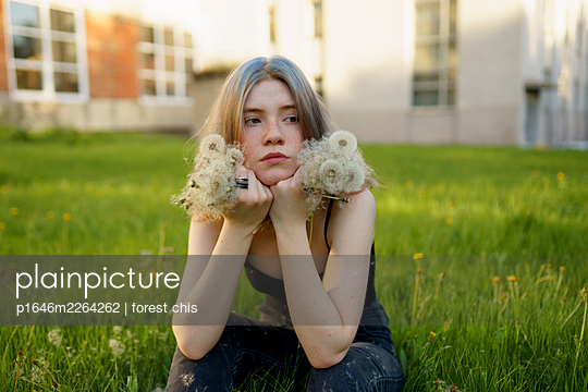 Young woman sits in a meadow holding dandelion clocks - p1646m2264262 by Slava Chistyakov