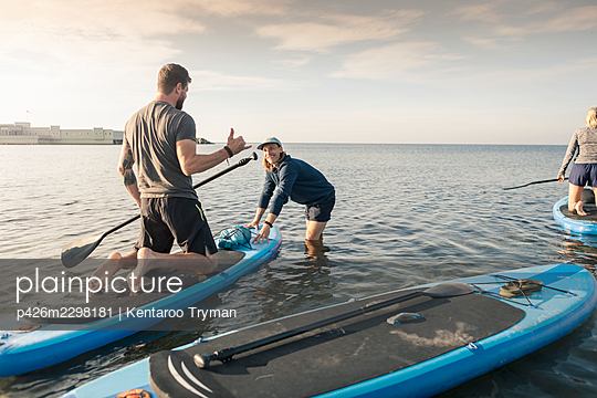 Man learning to paddleboard from male instructor in sea at beach - p426m2298181 by Kentaroo Tryman