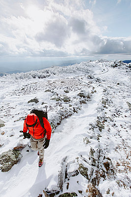 High angle view of backpacker wearing warm clothing walking on snow during winter - p1166m2001278 by Cavan Images