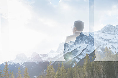 Digital composite businessman at window looking at mountains - p1192m1116646f by Hero Images