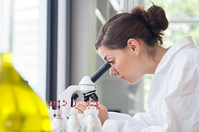 Portrait of young female chemist looking through microscope - p300m950694f by Sigrid Gombert