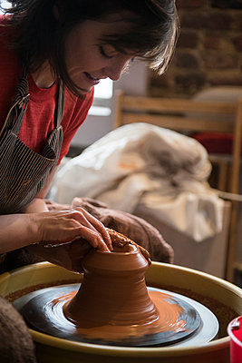 Caucasian woman shaping pottery clay on wheel - p555m1481944 by JGI/Jamie Grill