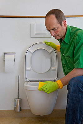 Man cleaning the toilet - p8110042 by Werner Dieterich