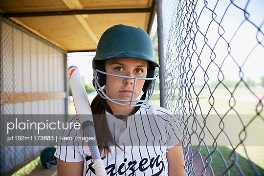 Portrait serious middle school girl softball player wearing batting helmet and holding bat in dugout