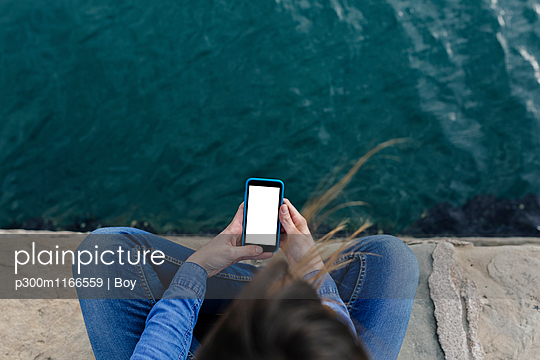Young woman sitting on dock using cell phone - p300m1166559 by Boy photography