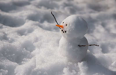 Close up of a small snowman sitting on the the snow. - p1166m2095437 by Cavan Images