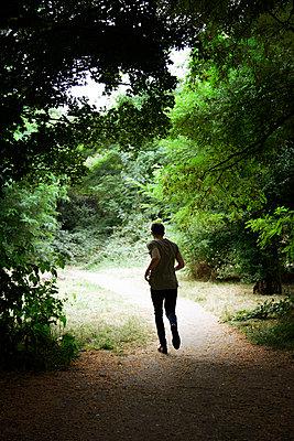 Mann rennt auf einem Waldweg - p1248m1590739 von miguel sobreira