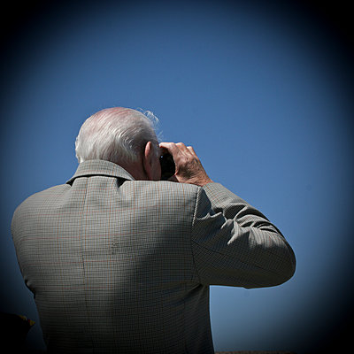 Old man looking with binoculars - p1513m2039179 by ESTELLE FENECH