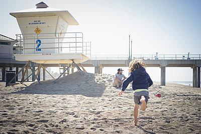 Caucasian boy running to father on beach - p555m1305176 by Alberto Guglielmi
