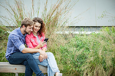Couple sitting together on park bench, looking at smartphone - p623m1221424 by Gabriel Sanchez