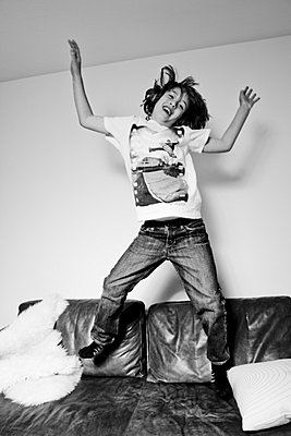 Boy jumping on a sofa - p9070012 by Anna Fritsch