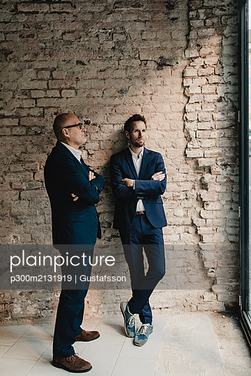 Senior and mid-adult businessman standing at brick wall - p300m2131919 by Gustafsson