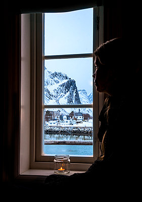 Pensive woman looking out window at snowy mountain, Reine, Lofoten Islands, Norway - p1023m2067623 by Anna Wiewiora