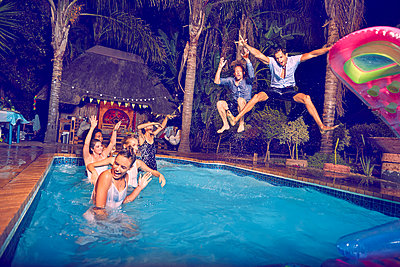 Exuberant young men friends jumping into swimming pool at night - p1023m2187430 by Trevor Adeline