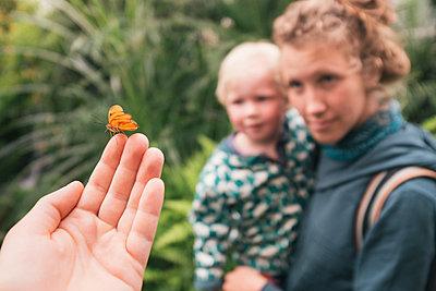 Mutter und Sohn betrachten Schmetterling - p1046m1220951 von Moritz Küstner