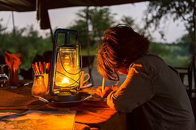 Six year old boy writing a journal by lantern light in a tented camp. - p1100m2214589 by Mint Images