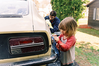 A father and his toddler daughter washing a classic car together. - p1166m2190685 by Cavan Images